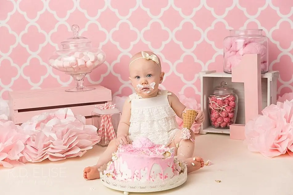 Baby girl in a white outfit eating cake during her candy themed cake smash with Pueblo photographer K.D. Elise Photography.