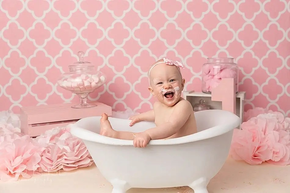Happy baby girl in a plastic clawfoot bathtub after her candy themed cake smash with K.D. Elise Photography, a photographer in Colorado Springs.