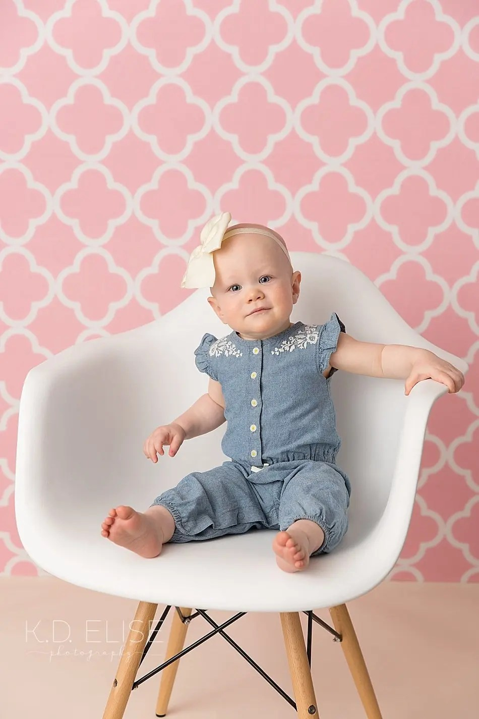 Smiling baby girl in a blue outfit sits a white chair for first birthday portraits with K.D. Elise Photography, a photographer in Pueblo, CO.