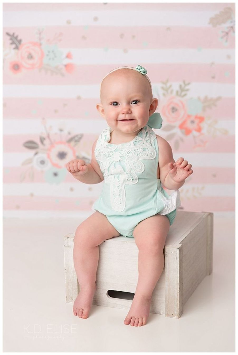 Baby girl sitting on a crate in front of a pink and white stripped backdrop.
