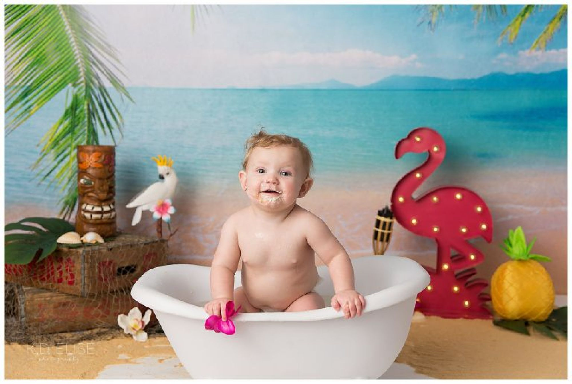 Baby girl in bathtub after luau themed cake smash from K.D. Elise Photography.