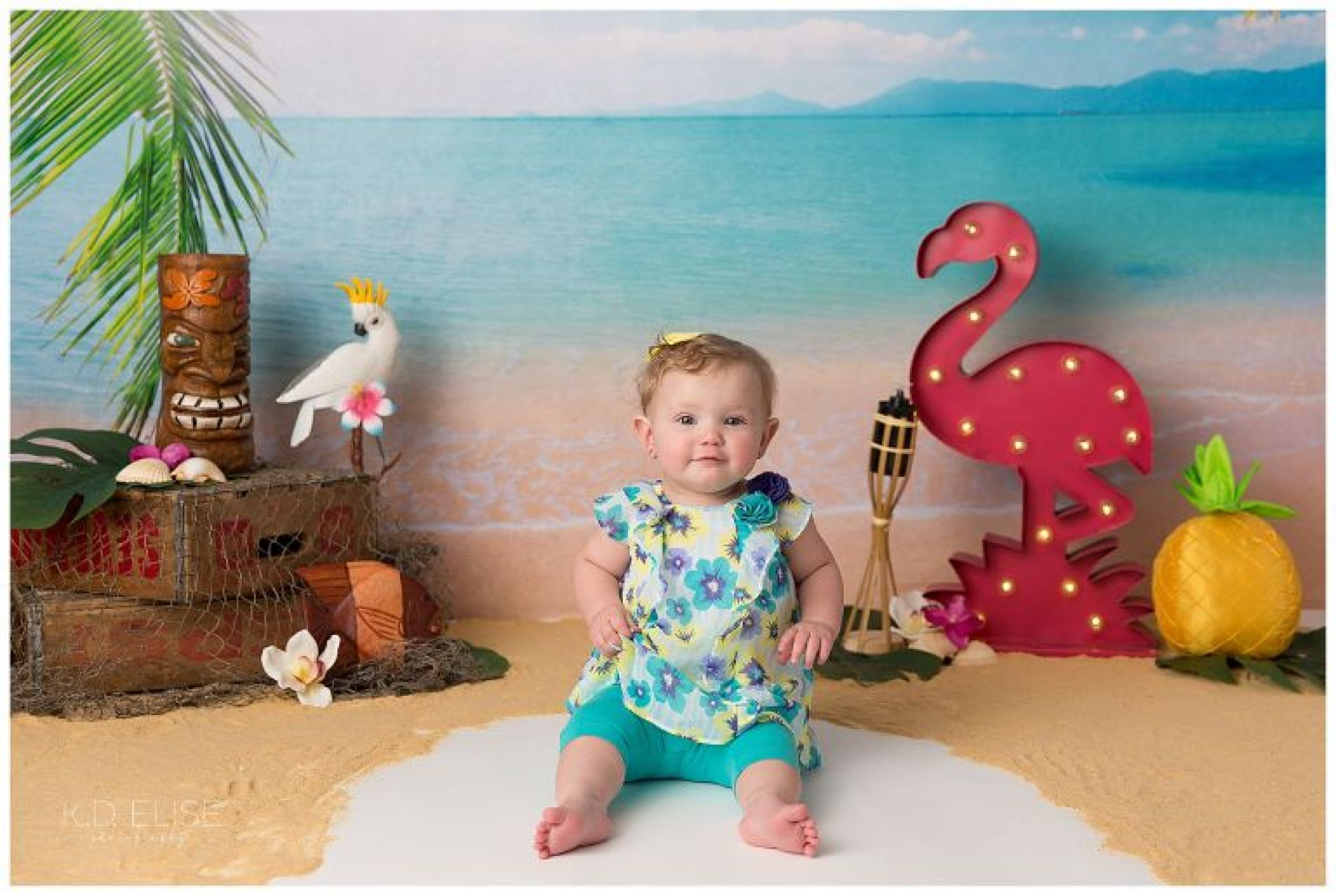 First birthday portrait of baby girl sitting on a blue chair in front of luau themed cake smash backdrop.