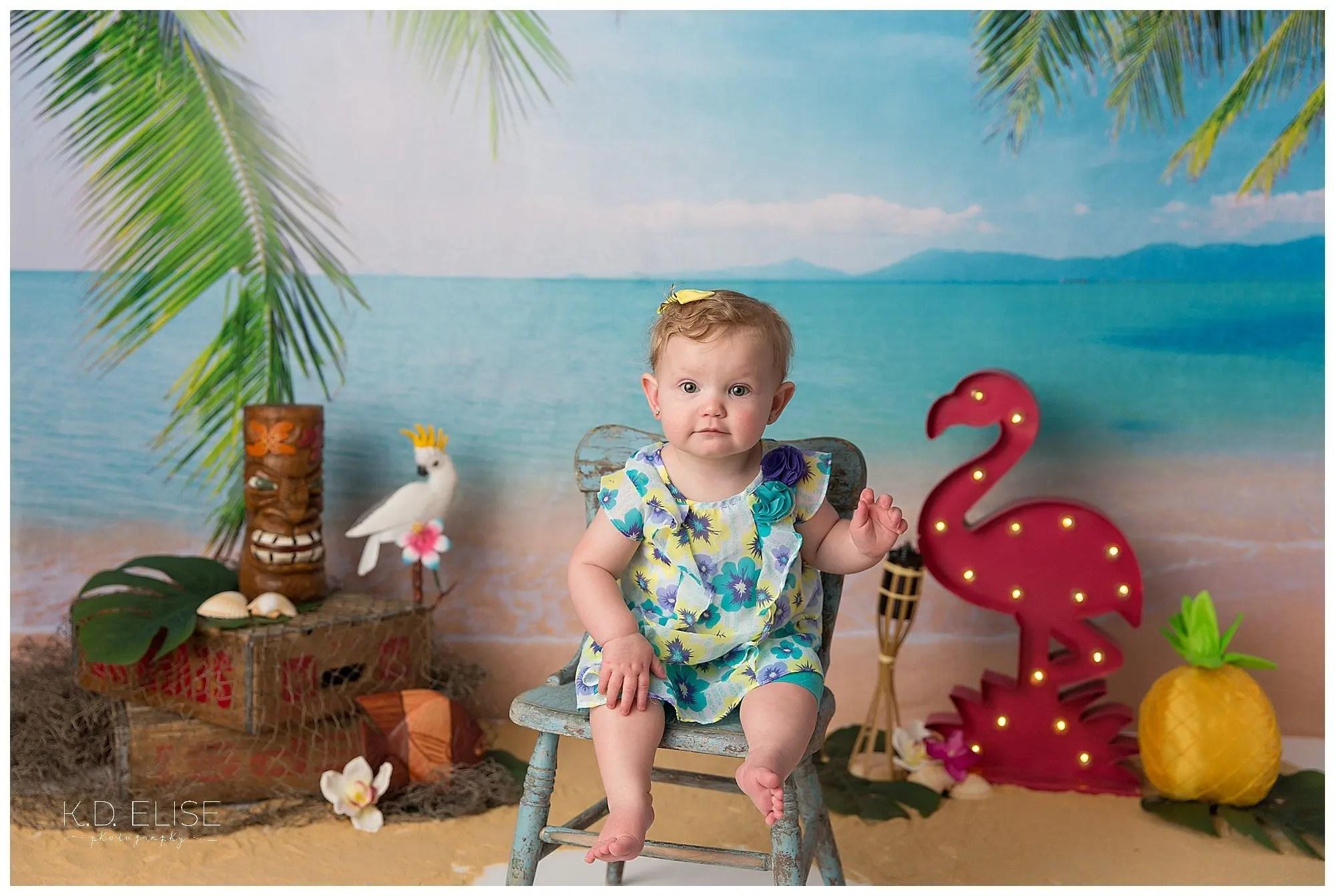 First birthday portrait of baby girl on luau themed cake smash backdrop.