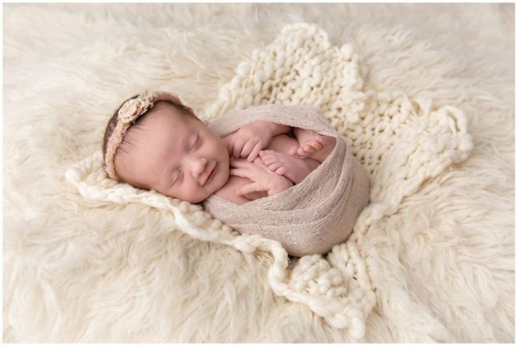 Newborn baby girl wrapped in pink, laying on a cream fur.