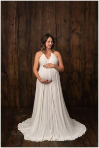 In studio maternity photography image of pregnant mom in a cream gown on wood backdrop.