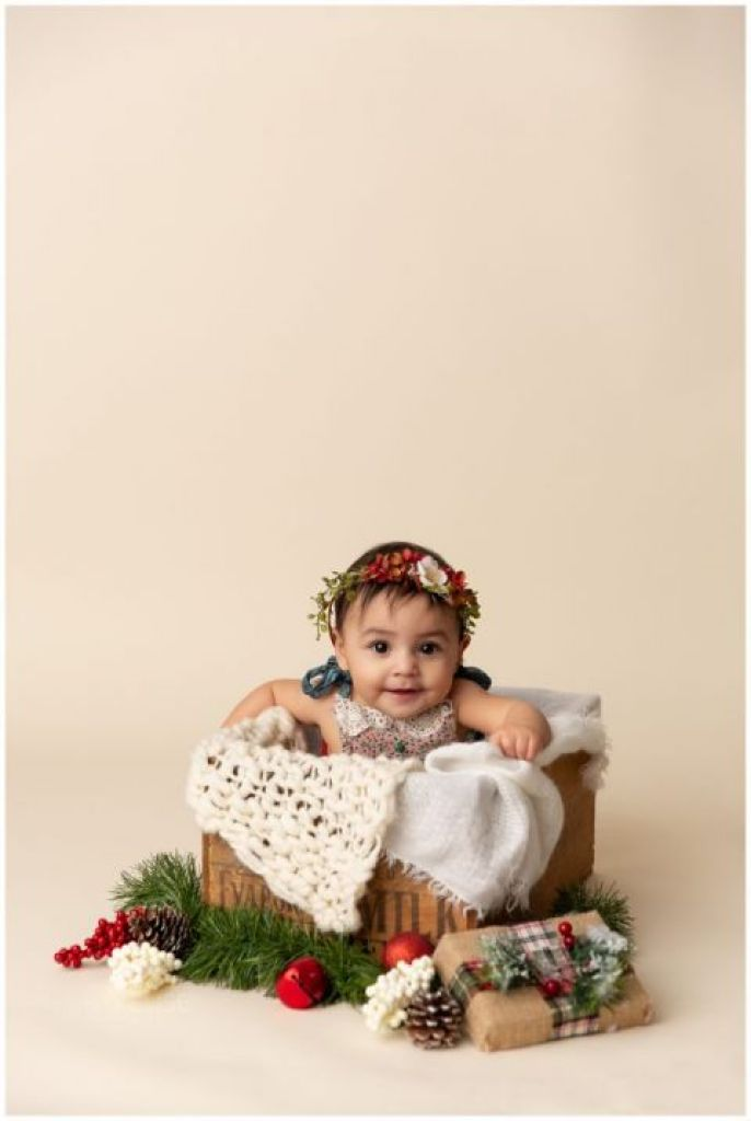 Baby girl in a Christmas out and floral headband sitting in a wooden crate. Six month milestone session by K.D. Elise Photography.
