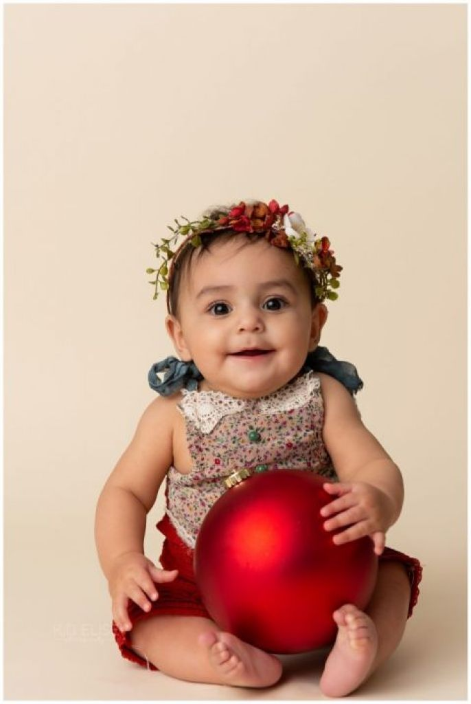 Baby girl holding a red Christmas ornament during milestone session.
