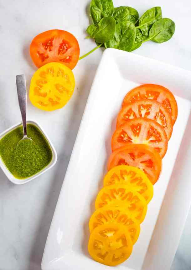 sliced heirloom tomatoes with basil sauce on the side