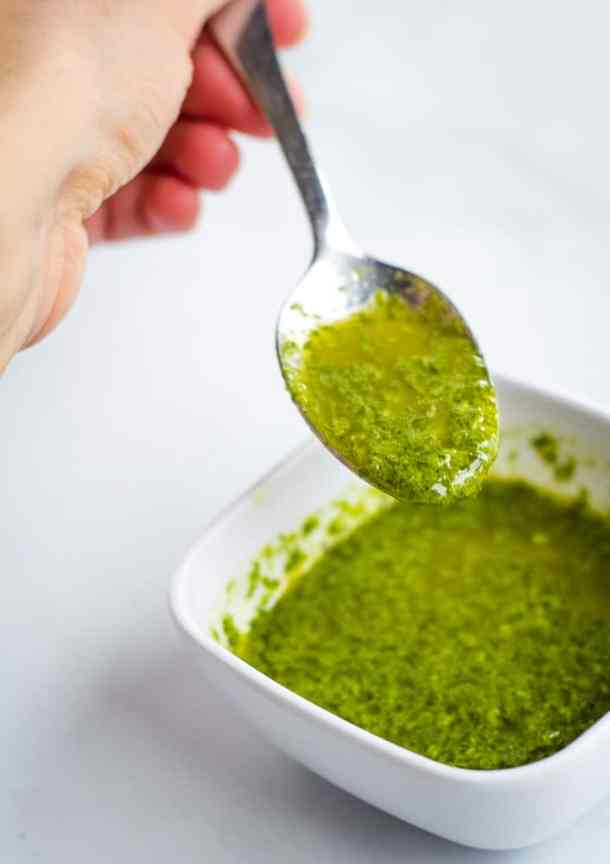 spoonful of basil sauce over white bowl
