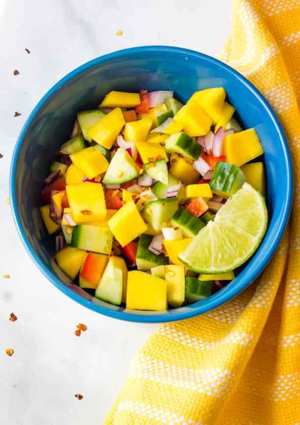 overhead of mango cucumber salad in blue bowl with yellow dish towel