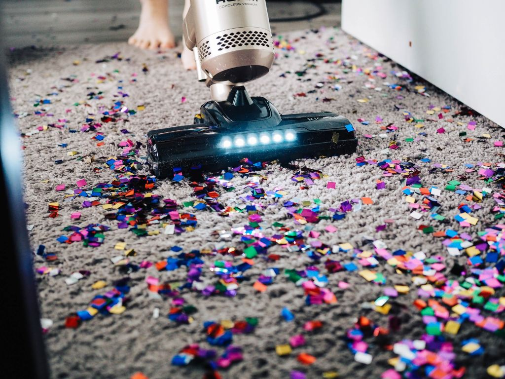 Should you hire a cleaning service? Person vacuuming glitter