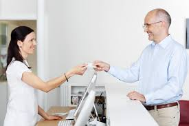 Patient handing health card to secretary-Dental Financing