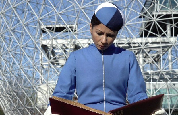 Woman wearing a blue coat and reading a book