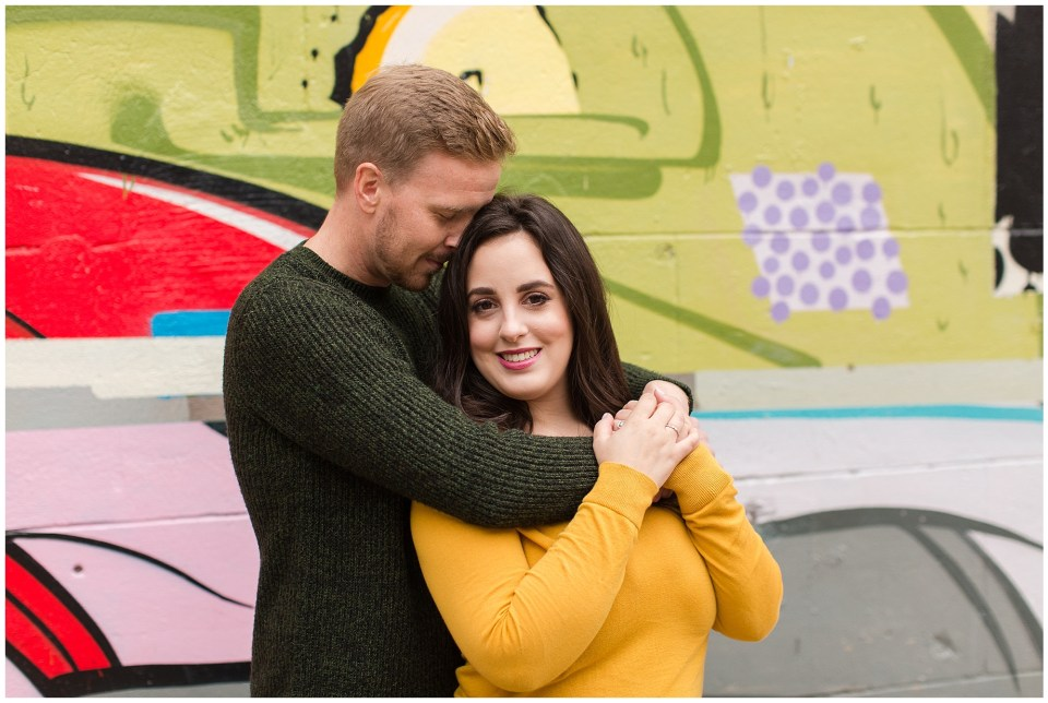 couple posing in front of graffiti wall