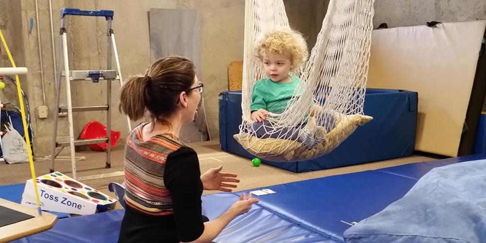 boy sitting in a hammock swing in an occupational therapy session