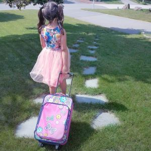 little girl from the back toting a suitcase down a grassy hill
