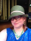 Kelly is modeling her green straw hat in a cloche style with brown ribbon piping around the brim and a taupe ribbon around the crown.