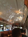 Interior view of a New Orleans street car featuring a concave white aluminum ceiling and wooden seats for passengers.