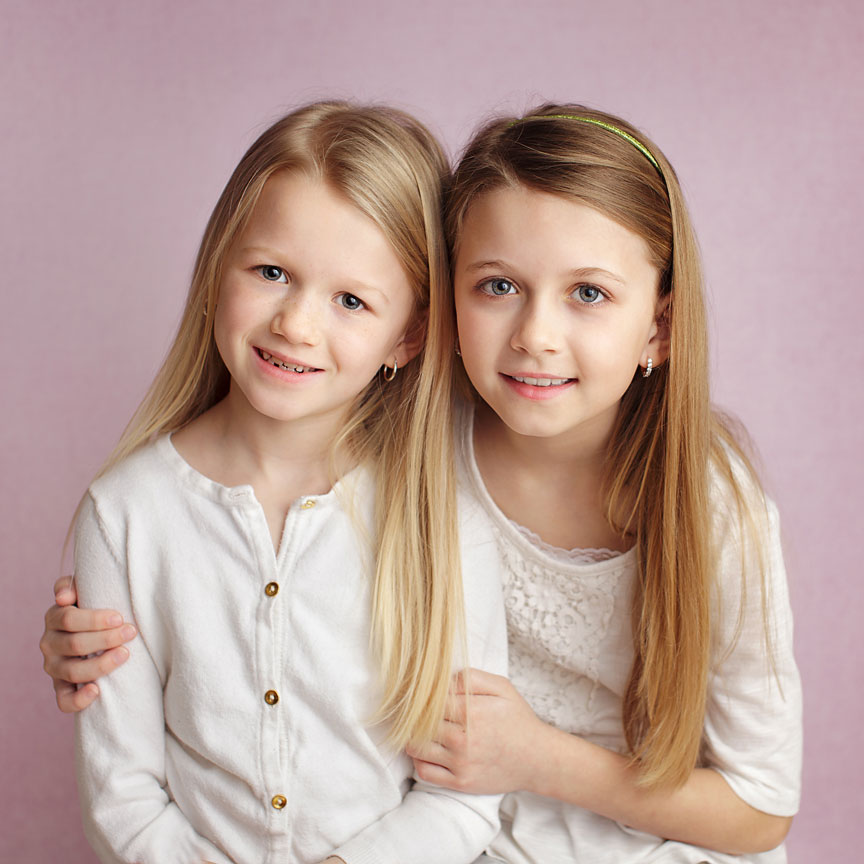 Young sisters on pink backdrop