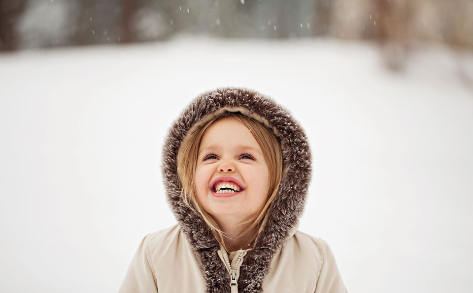 young girl watching snow fall
