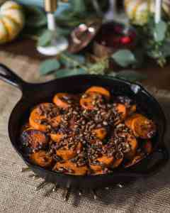 cast iron skillet with cooked, sliced sweet potatoes topped with toasted pecans on a table with thanksgiving decorations