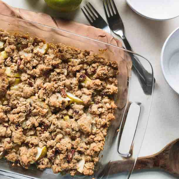 apple crisp in a casserole dish with bowls nearby