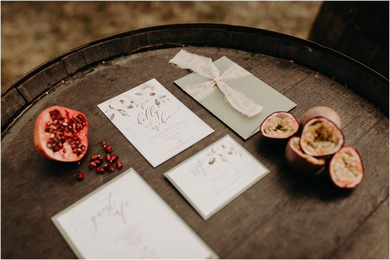 Rustic wedding stationary set laid out on a wooden barrel at this Essex boho wedding