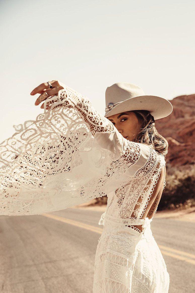 boho bride wearing a cowboy hat waves her rue de seine wedding dress lace sleeve