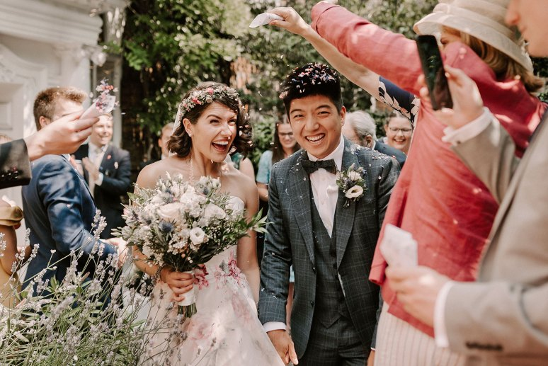Bride and Asian groom leave wedding venue to confetti throwing exit