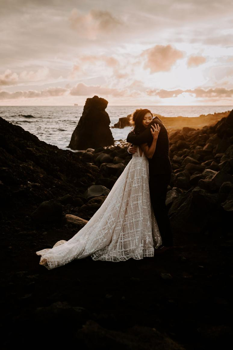 Warm sunset with wedding couple hugging by the sea captured by Iceland elopement photographer