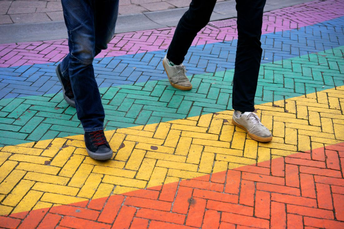 Men walking on colorful crosswalk
