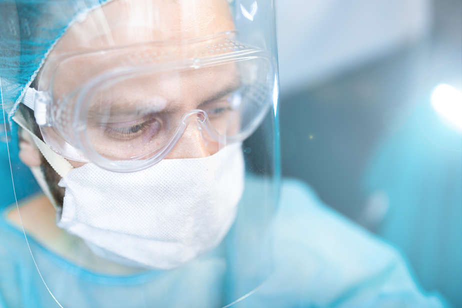 Close-up of a doctor wearing goggles, a hairnet, and a surgical mask underneath a face shield.