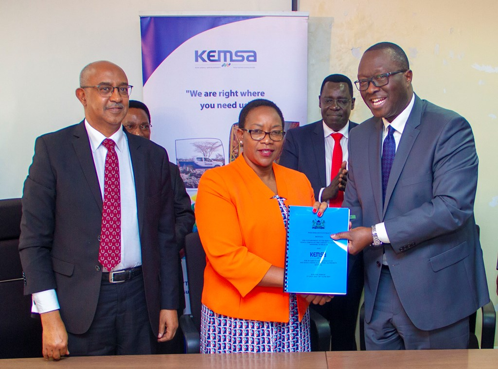 Health CS Sicily Kariuki and Acting Board Chairman Mr.Andrew Onyach display the signed PC. Looking on is a senior MoH official.