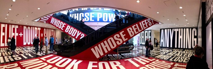 "Escalators in museum surrounded by display with large words: ""Belief + Doubt = Sanity"", ""Believe Anything"", ""Whose Body?"" ""Whose Beliefs?"""
