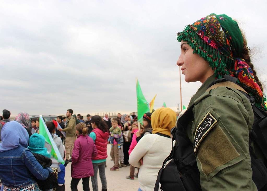 A woman in military fatigues and traditional headscarf overlooks a group of civilians of all ages.