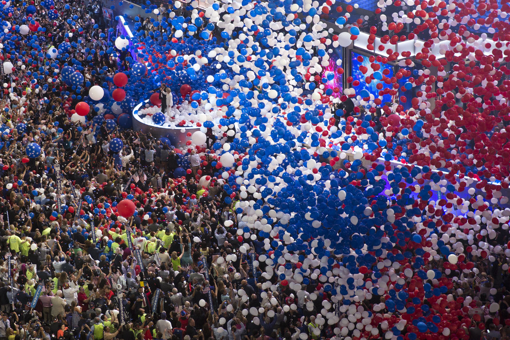 Red, white and blue balloons fall over the crowd on the floor of a large convention