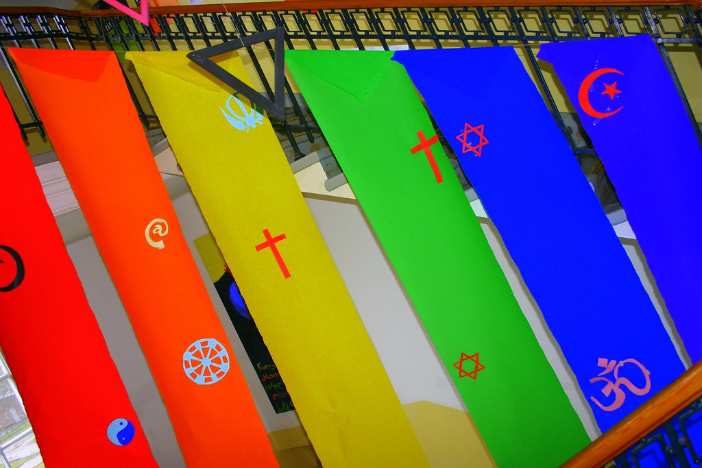 A series of banners in rainbow colors feature symbols from different religions
