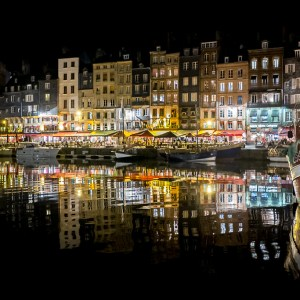 Nightime reflections in the harbour at Honfleur, France.