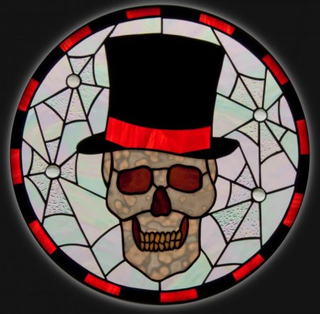 Cobweb Eddy PDF pattern for a 17 inch diameter stained glass panel featuring a skull in top hat surrounded by cobwebs black and orange glass.