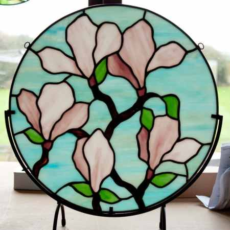 Round Magnolia in a stand, 16 inch round stained glass magnolia panel in window stand, pink flowers on a turquoise background.