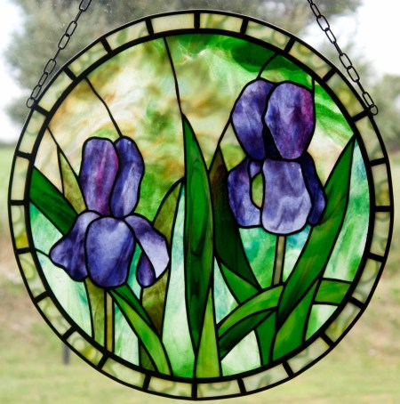 Two Irises with Border, two purple irises against a green and amber background with light green mottles border pieces.