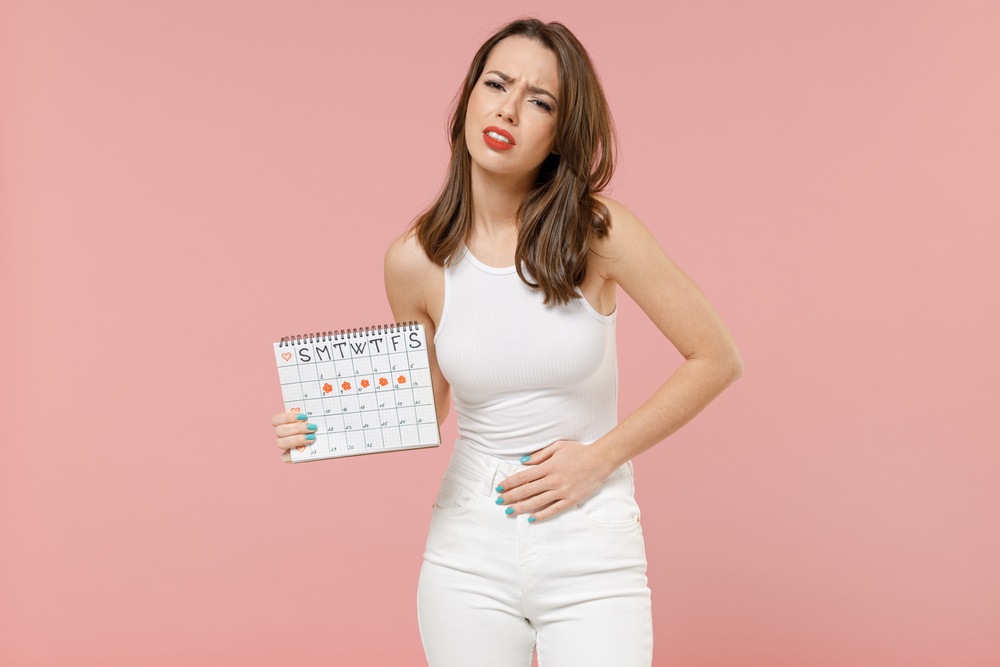 Young suffering woman in white clothes hold in hand female periods calendar checking menstruation days put arm on belly