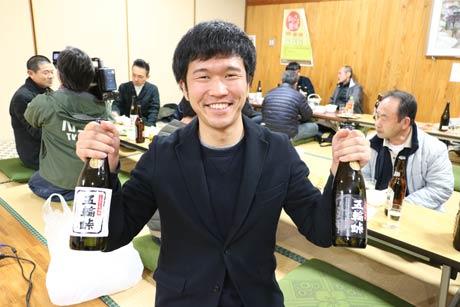 完成した下田産本格芋焼酎「五輪峠」を手に「芋主プロジェクト」に中心となって担当した地域おこし協力隊の大滝さん