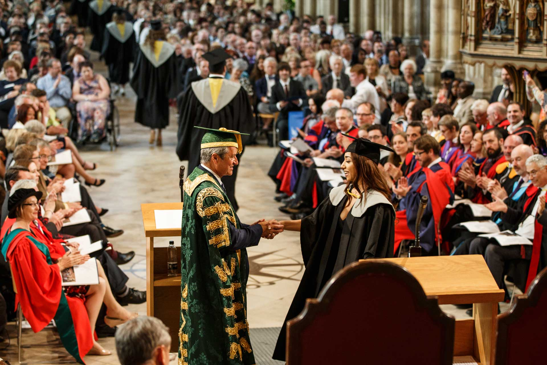 Gavin Esler giving award at graduation ceremony in Canterbury Cathedral