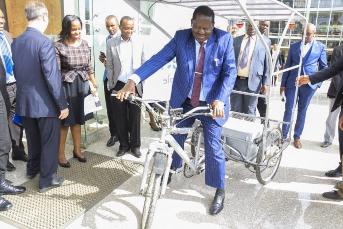 Energetic Raila rides on an e-bicycle during global energy conference