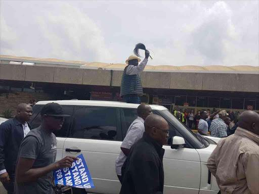 Opposition leader Raila Odinga greets his supporters outside the JKIA in Nairobi