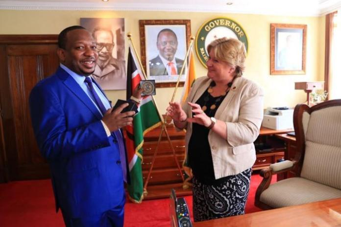 Victoria Wallace, the Director-General of the Commonwealth War Graves Commission hands Nairobi Governor Mike Sonko a special commendation seal, December 2.