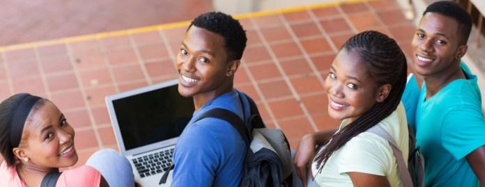 Teens smiling up at camera.