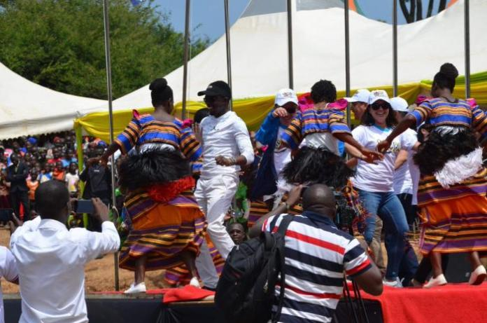 Foreign Affairs and Trade CAS Ababu Namwamba (black baseball hat) joins in on a dance during the 2019 edition of the Isambo Beach Festival.