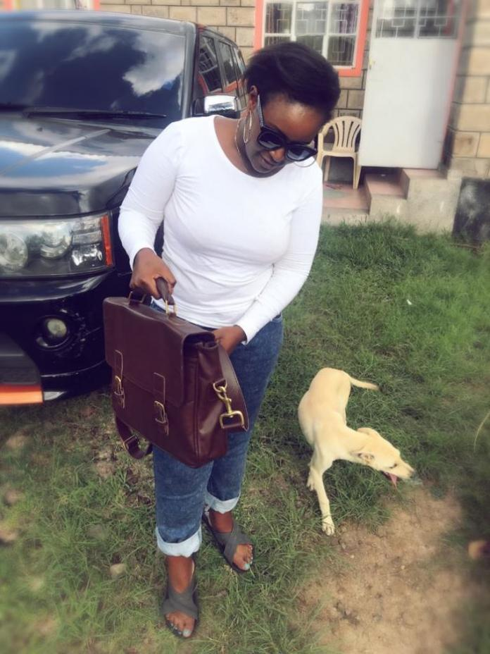 A photo of Mercy Kyallo displaying a product made by Yallo Leather Company